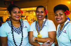 3 lady staff member from Tanoa Skylodge Hotel standing infront of a bar